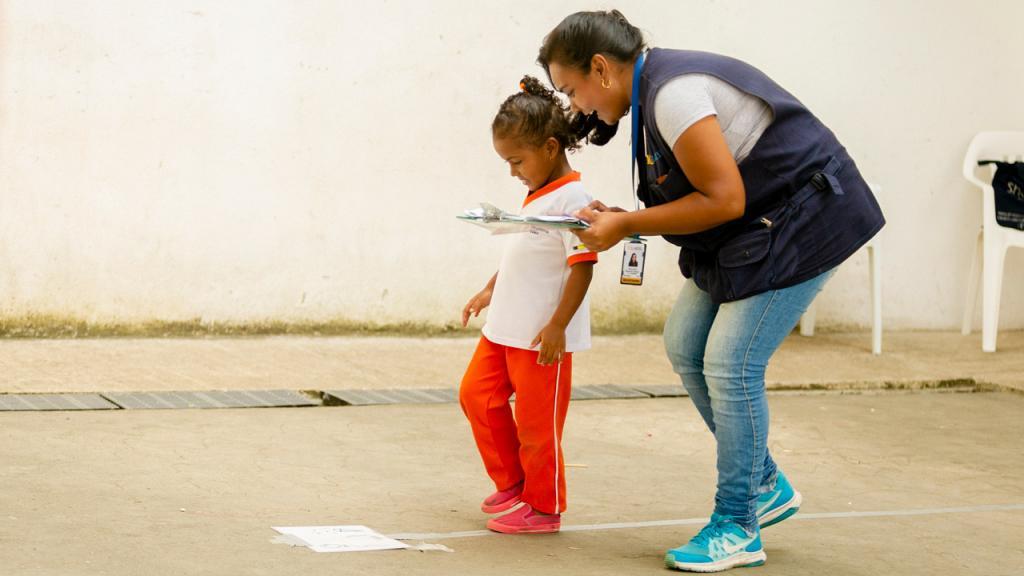 Una mujer le ayuda a caminar a un niño