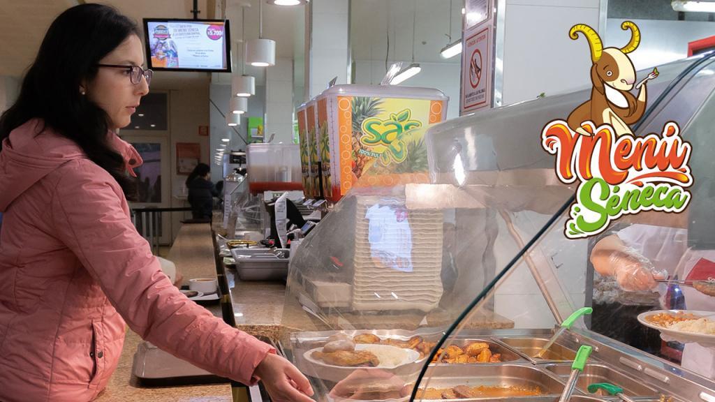 Imagen de una estudiante recibiendo su almuerzo en la cafetería