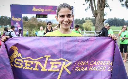 Mujer celebra luego de ganar en la carrera Senek 2016.