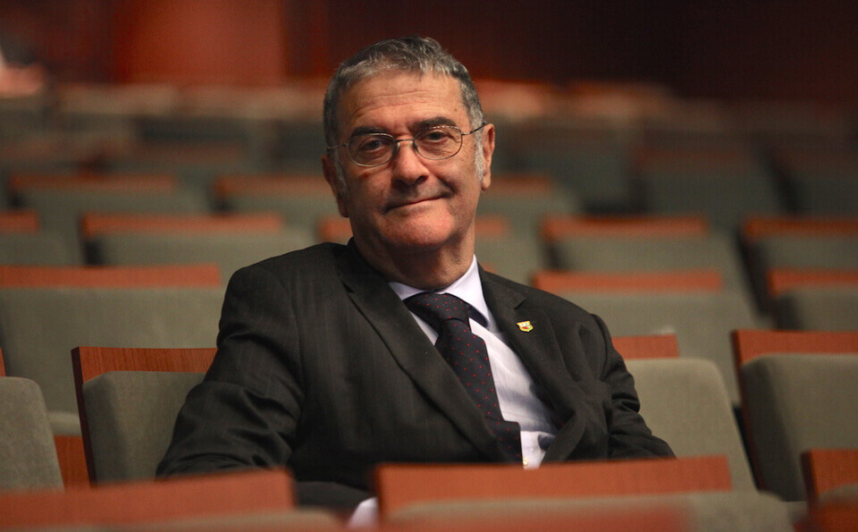 hombre sonriendo sentado en un auditorio vacío