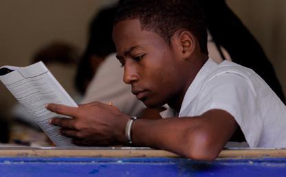 Estudiante sentado en un pupitre presenta un examen