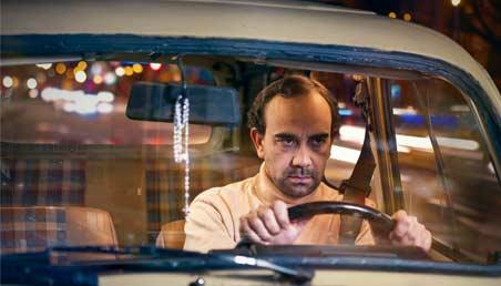 Imagen de la película Sin mover los labios. El protagonista maneja, furioso, un carro.