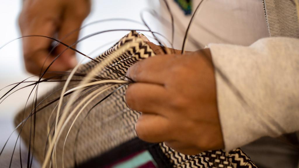 Manos tejiendo un bolso en caña flecha