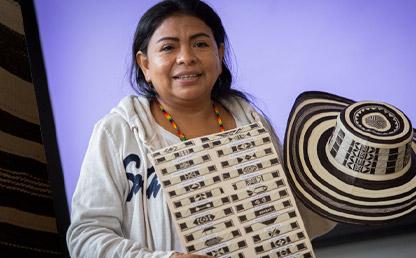 Mujer mostrando un sombrero vueltiao y los tipos de tejido que hay