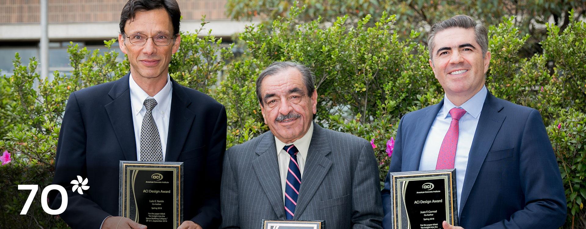 Tres profesores de la Universidad de los Andes exponen placas de reconocimiento.