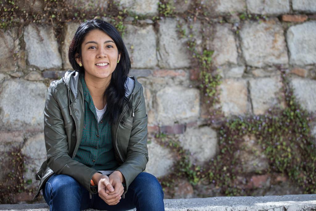 una joven sentada en unas escaleras sonríe a cámara
