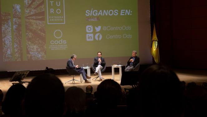 Imagen de 3 hombres sentados hablando en la tarima de un teatro