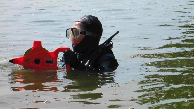 Persona con traje de buzo llevando una máquina para investigar