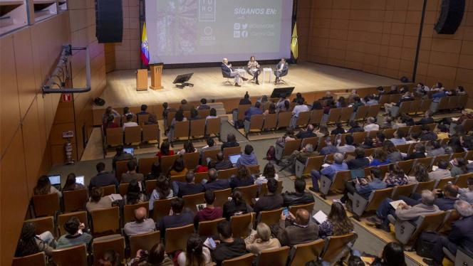 Personas en un auditorio, escuchando una conferencia