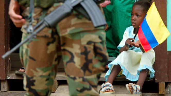 Imagen de una niña pequeña con una bandera de Colombia en sus manos