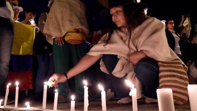 Mujer encendiendo unas velas en una marcha por la paz