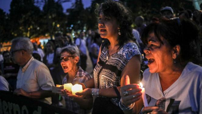 Grupo de mujeres sosteniendo una vela en una marcha por la Paz