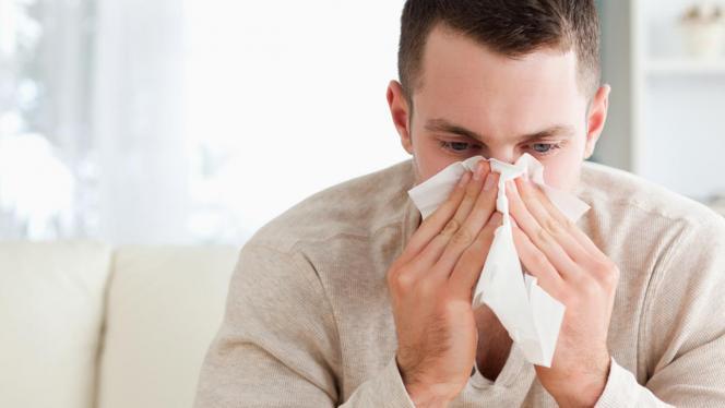 Hombre sonándose la nariz con un pañuelo