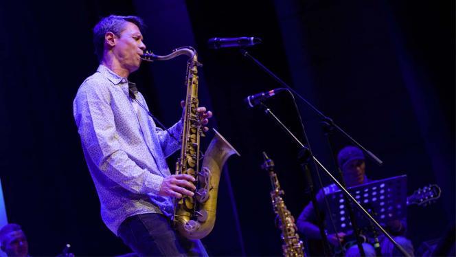 Hombre tocando saxofón en un concierto