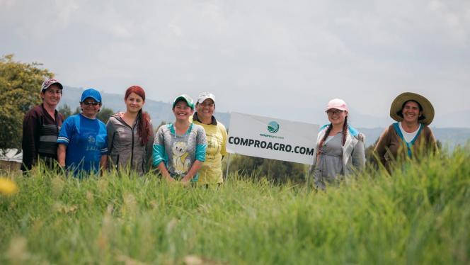 Grupo de mujeres campesinas con un cartel de comproagro.com