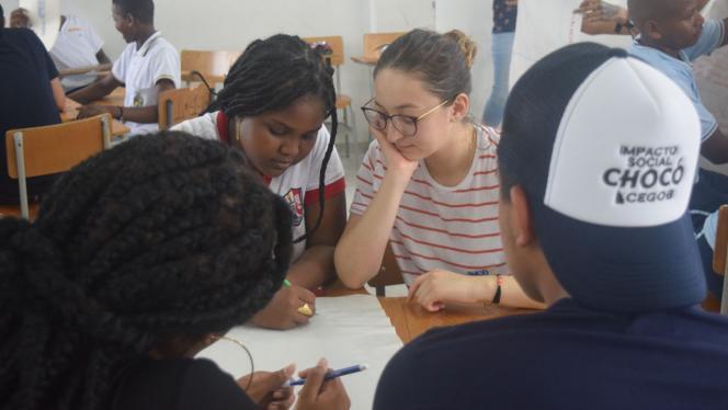 Imagen de estudiantes en una mesa haciendo un trabajo