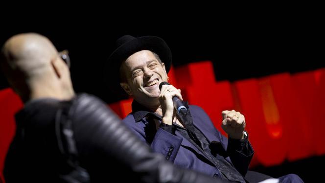 Hombre riendo con un micrófono en la mano