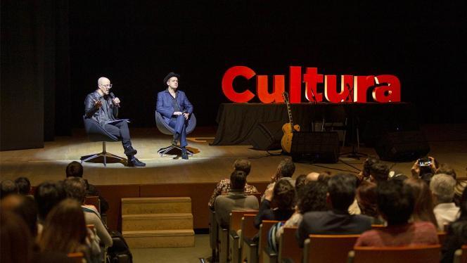 Hombre dando una conferencia, atrás un aviso la palabra cultura