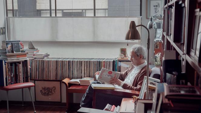Hombre en una biblioteca sentado leyendo un libro