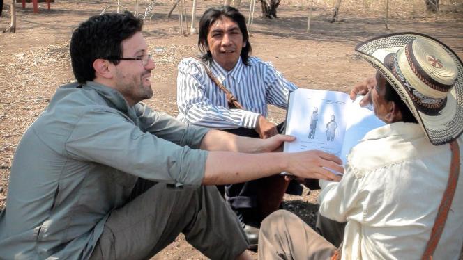 Imagen de 2 hombres mostrándole un libro a un indígena