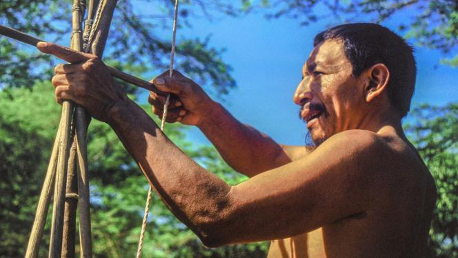 Imagen de hombre indígena con un arco elaborado en palos