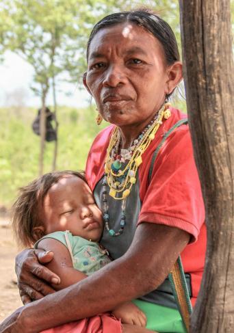 Fotografía de una mujer indígena con una niña en sus brazos dormida