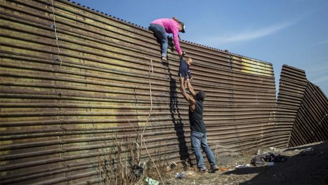 Familia de migrantes cruzando sobre un muro
