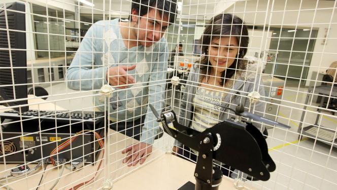 Un hombre y una mujer mirando un elemento de un laboratorio