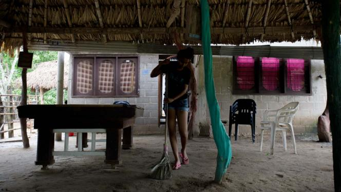 Mujer barriendo una casa en el campo