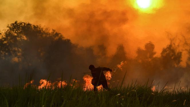 Imagen de un hombre corriendo en medio de un incendio climático