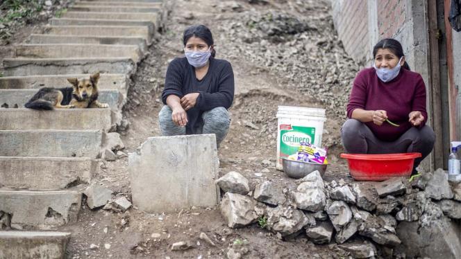 Dos mujeres en la entrada de su casa, en un barrio vulnerable.