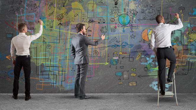 Imagen de 3 hombres escribiendo en la pared