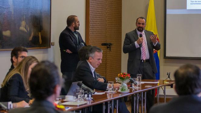 Hombre dando un discurso en el comité de la Tríada Uniandes