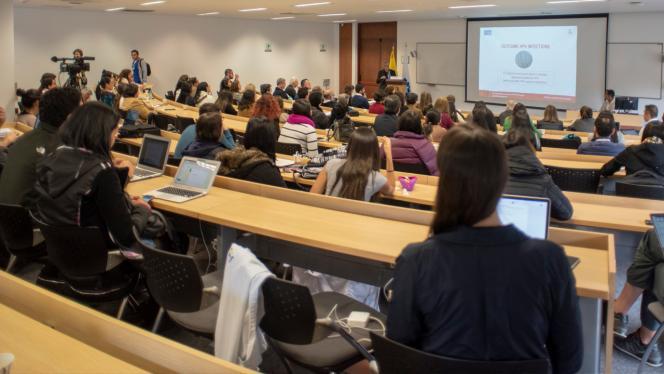 Grupo de personas en un salón tomando una clase