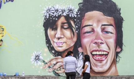 Jóvenes observan mural en homenaje a Margarita Gómez y Mateo Matamala