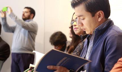 Estudiante con el libro 'Emprendedores en crecimiento, el reto de la financiación', en la Universidad de los Andes