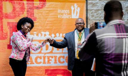 Hombre y mujer de la comunidad afro estrechan la mano.