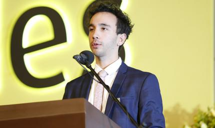 Julián Enrique Niño estudiante que recibió la distinción ofreciendo un discurso en la ceremonia de grados de la Unievrsidad de los Andes