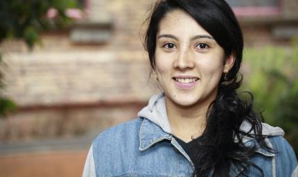Stefanía Peña, estudiante que recibió distinción, delante de un edificio en la Universidad de lo Andes