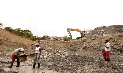 Mineros artesanales del Chocó, en Colombia. Junto a ellos, en el río, una máquina extractora.