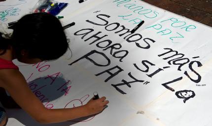 niña haciendo letrero sobre la paz para una marcha