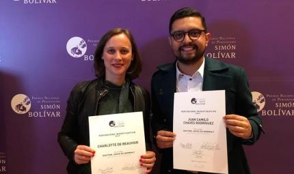 Dos personas, ganadoras del Premio Simón Bolívar, posan con un diploma