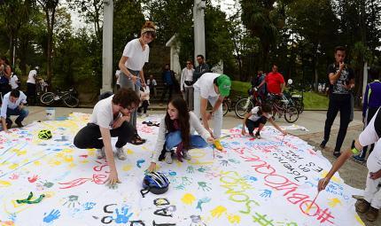 Jóvenes pintando banderas blancas con mensajes de paz.