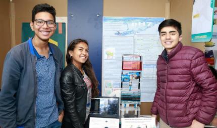 Tres estudiantes posando en el stand para la foto