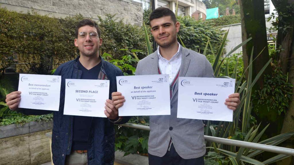 Ariel Andrés Sánchez Rojas y Santiago Eduardo Gómez Cifuentes, estudiantes de la Universidad de los Andes, presentan sus diplomas.
