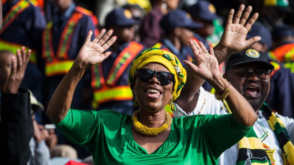 Mujer sudafricana con vestido verde y pañoleta amarilla sonríe y alza sus manos.