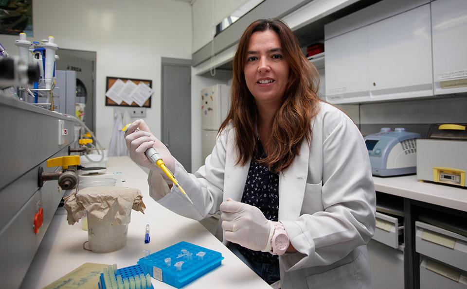 mujer con bata en un laboratorio tomando muestras