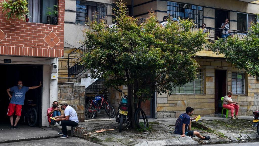 Apartamentos y casa con personas asomadas