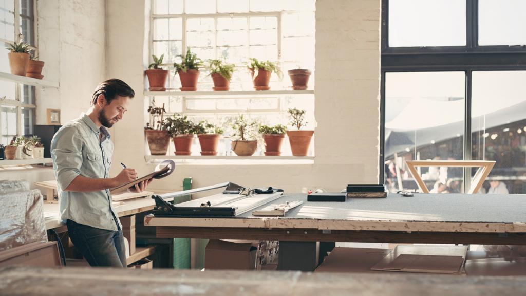 Emprendedor tomando nota en su taller decorado con plantas