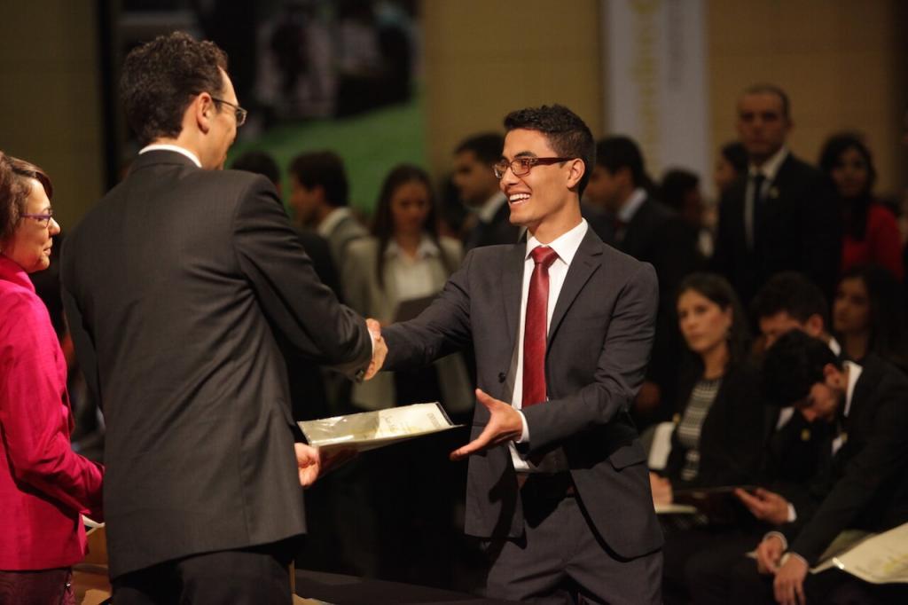 joven de corbata vinotinto recibe diploma de dos personas